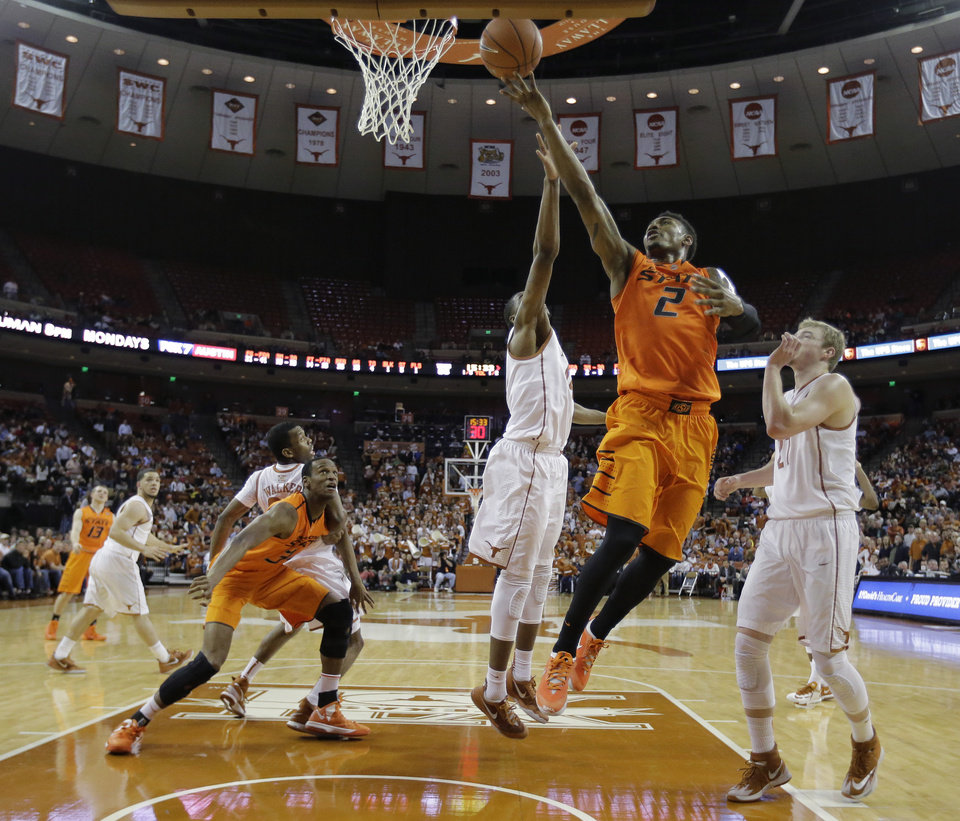 Photo - Oklahoma State's Le'Bryan Nash (2) drives between Texas' Prince Ibeh (44) and Connor Lammert (21) to score during the second half on an NCAA college basketball game, Tuesday,  Feb. 11, 2014, in Austin, Texas. Texas won 87-68. (AP Photo/Eric Gay)