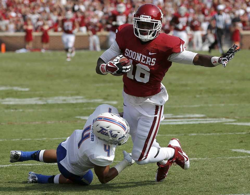 Photo - Oklahoma's Jaz Reynolds (16) is brought down by Tulsa's Darnell Walker (4) after a long reception during a college football game between the University of Oklahoma Sooners (OU) and the Tulsa Golden Hurricane at Gaylord Family-Oklahoma Memorial Stadium in Norman, Okla., on Saturday, Sept. 14, 2013. Photo by Bryan Terry, The Oklahoman