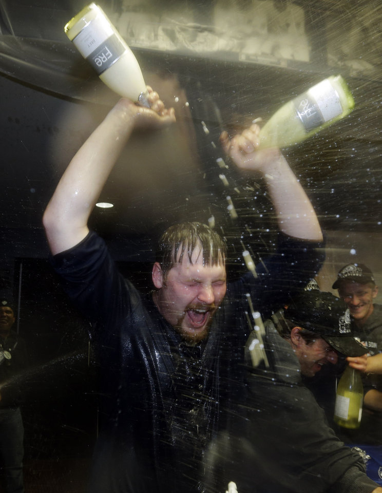 Photo -   Detroit Tigers' Phil Coke gives himself a celebratory dousing in the locker room after his team won Game 4 of the American League championship series 8-1, against the New York Yankees, Thursday, Oct. 18, 2012, in Detroit. The Tigers move on to the World Series. (AP Photo/Paul Sancya)