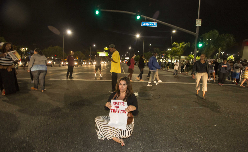 Photo - A demonstrator with a sign sits on the intersection of Crenshaw Boulevard and Coliseum street during a protest in Los Angeles on Sunday, July 14, 2013, the day after George Zimmerman was found not guilty in the shooting death of Trayvon Martin. Seventeen-year-old Martin was shot and killed in February 2012 by neighborhood watch volunteer George Zimmerman.  (AP Photo/Ringo H.W. Chiu)