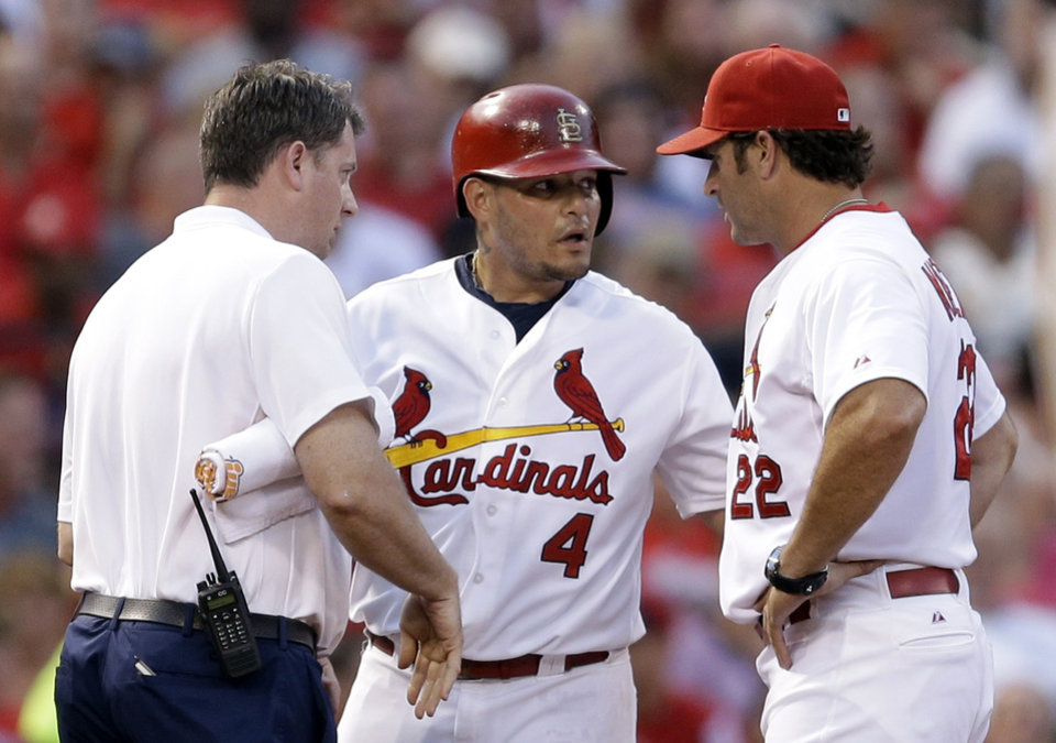 Photo - St. Louis Cardinals' Yadier Molina, center, is checked on by manager Mike Matheny, right, and trainer Chris Conroy after injuring his hand while sliding into third during the second inning of a baseball game against the Pittsburgh Pirates Wednesday, July 9, 2014, in St. Louis. Molina finished the inning but was replaced in the third inning by Tony Cruz. (AP Photo/Jeff Roberson)