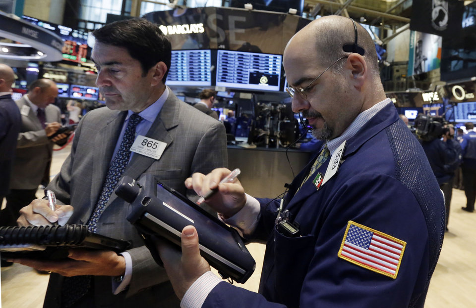 Photo - Traders Mark Muller, left, and Luigi Muccitelli work on the floor of the New York Stock Exchange Tuesday, May 27, 2014. Stocks rose Tuesday after the government reported that orders for big-ticket items rose unexpectedly last month. (AP Photo/Richard Drew)