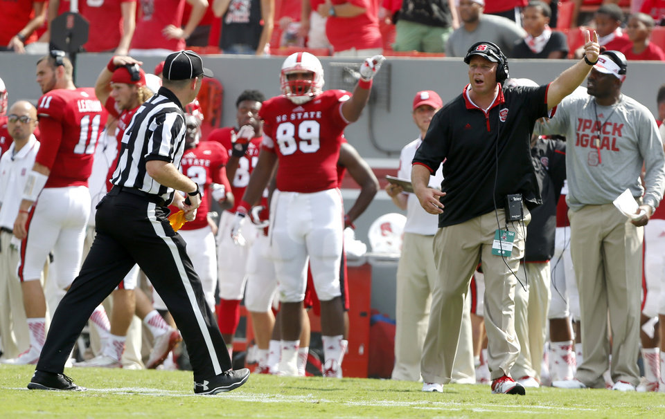 Photo - North Carolina State head coach Dave Doeren motions to the officials during the second half of an NCAA college football game against Georgia Southern, Saturday, Aug. 30, 2014, in Raleigh, N.C. N.C. State won 24-23. (AP Photo/The News & Observer, Ethan Hyman)