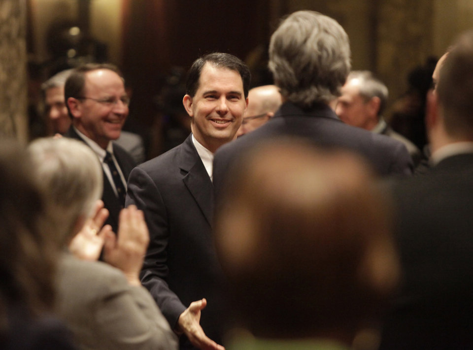 Wisconsin Governor Scott Walker greets legislators while making his way into the Assembly chamber for his state budget address at the Wisconsin State Capitol in Madison, Wis. Wednesday, February 20, 2013. (AP Photo/Wisconsin State Journal, John Hart)