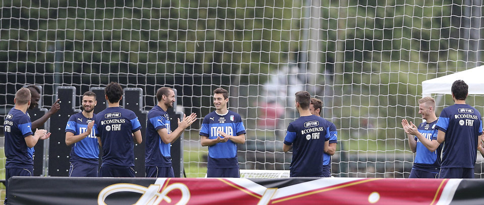Photo - Italy's Mario Balotelli, second from left, responds as his fellow teammates applaud his marriage proposal, during a training session in Mangaratiba, Brazil, Tuesday, June 10, 2014. Balotelli took care of some personal business before the World Cup training session, proposing to his Belgian girlfriend Fanny Neguesha early Tuesday morning.