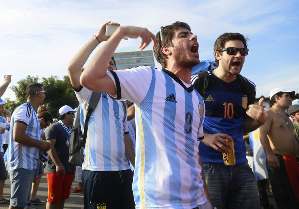 Photo - Argentina fans cheers, one day before their team's game against Nigeria, in Porto Alegre, Brazil, Tuesday, June 24, 2014. Authorities in this southern city, 430 miles from the Argentine border expected 80,000 Argentines to arrive for the World Cup match, only a quarter of them holding tickets for the game. While the fans had been good-natured so far, the city of about 1.4 million people was taking precautions. (AP Photo/Pedro Garcia)