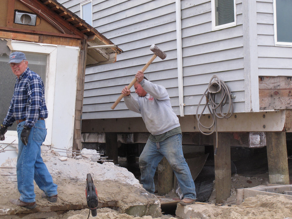 Workers dismantle shattered concrete in front of a storm-wrecked house on the beachfront in Manasquan, N.J., Saturday, May 25, 2013. Communities that were hard-hit by Superstorm Sandy, including Manasquan, are hoping for a profitable summer season to help them recover. (AP Photo/Wayne Parry)