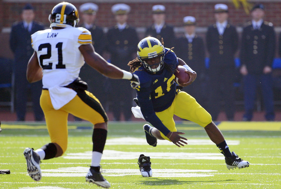 Michigan quarterback Denard Robinson (16) loses his shoe as he runs for a first down against Iowa defensive back Nico Law (21) during the first quarter of an NCAA college football game at Michigan Stadium in Ann Arbor, Mich., Saturday, Nov. 17, 2012. (AP Photo/Carlos Osorio)