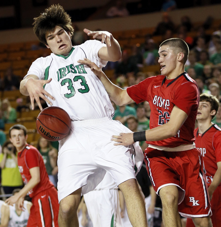 Photo - J.D. Limes (25) of Bishop Kelley knocks the ball away from Will Lienhard (33) of Bishop McGuinness during a Class 5A boys semifinal game in the state basketball championship tournament between Bishop McGuinness and Bishop Kelley at the Mabee Center in Tulsa, Okla., Friday, March 14, 2014. Photo by Nate Billings, The Oklahoman