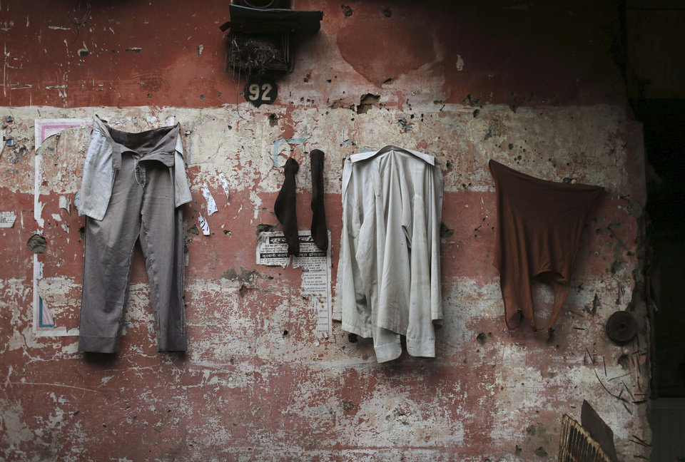 An Indian laborers clothing hangs to dry on a wall in a market on a cold morning in New Delhi, India, Monday, Jan. 7, 2013. North India continues to face below average weather conditions with dense fog affecting flights and trains. More than 100 people have died of exposure as northern India deals with historically cold temperatures. (AP Photo/Kevin Frayer)