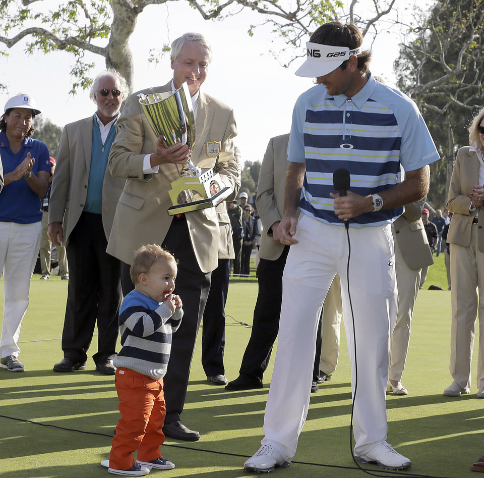 Photo - Bubba Watson is joined by his son Caleb at the ceremony after his victory in the Northern Trust Open golf tournament at Riviera Country Club in the Pacific Palisades area of Los Angeles, Sunday, Feb. 16, 2014. Watson carded a 15-under-par 269, two strokes ahead of the second-place finisher. (AP Photo/Reed Saxon)