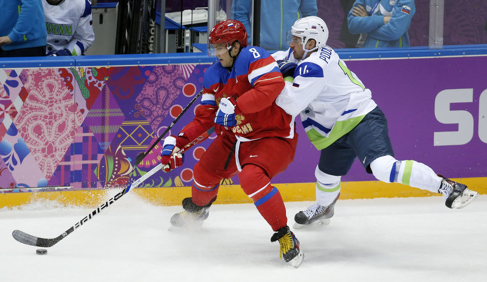 Photo - Russia forward Alexander Ovechkin, left, keeps the puck from Sovenia defenseman Matic Podlipnik in the first period of a men's ice hockey game at the 2014 Winter Olympics, Thursday, Feb. 13, 2014, in Sochi, Russia. (AP Photo/Mark Humphrey)