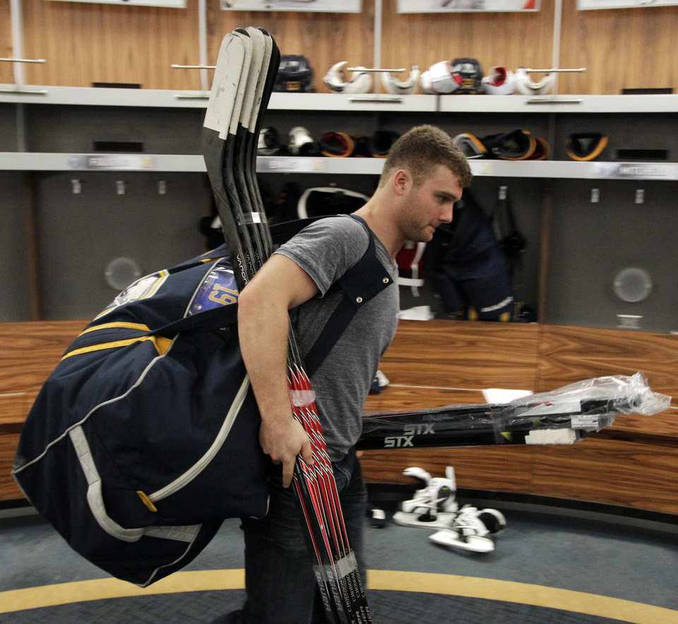 Photo - Buffalo Sabres center Cody Hodgson exits the Buffalo Sabres' locker room with his equipment after players gathered for the last time on Monday, April 14, 2014, after the NHL hockey team clinched the NHL's worst record, in Buffalo, N.Y. (AP Photo/Nick LoVerde)