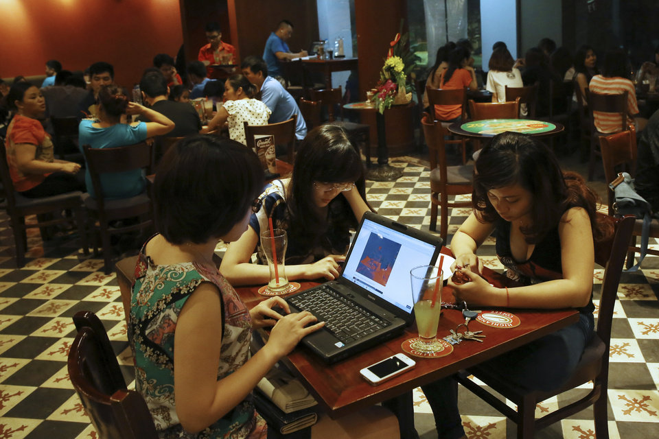 Photo - FILE - In this May 14, 2013 photo, three young Vietnamese women use a laptop and smart phones to go online at a cafe in Hanoi, Vietnam. Vietnamese pro-democracy activists and bloggers are battling a gathering campaign of blocking, hacking and spying by a shadowy pro-government army of cyber warriors. Although they can't prove it, activists and analysts strongly suspect the Vietnamese state is involved in the campaign, which is hampering the country's democracy movement. (AP Photo/Na Son Nguyen, File)
