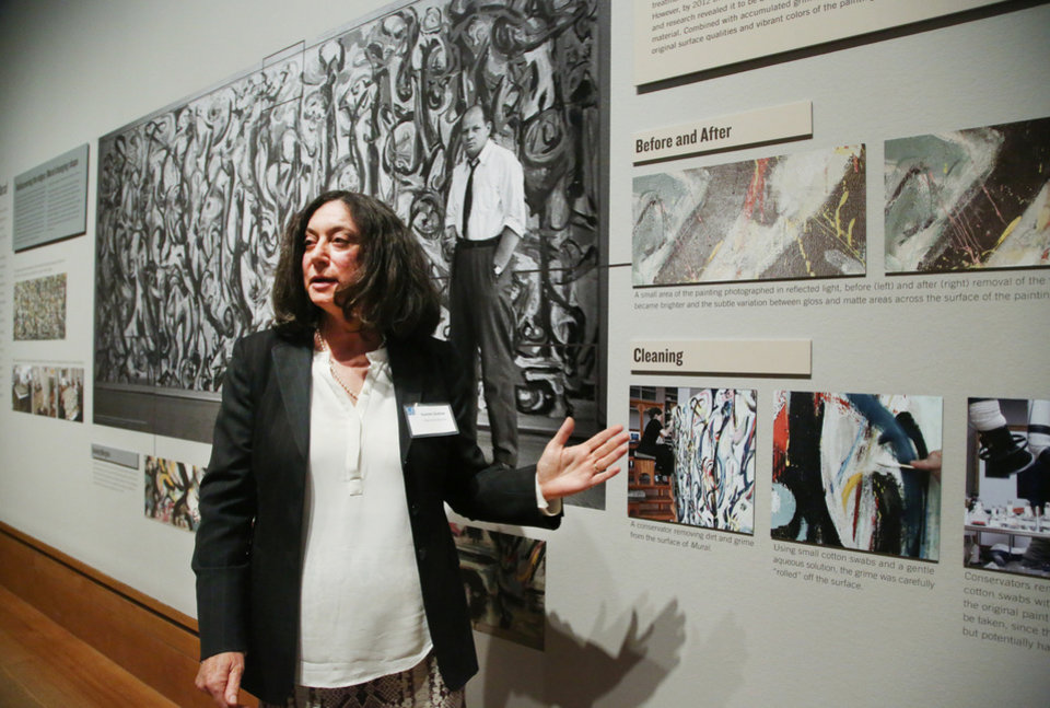"""Photo - Yvonne Szafran, head of paintings conservation at the Getty Museum  comments on the conservation treatment of Jackson Pollock's """"Mural,"""" 1943, during a media preview at the J. Paul Getty Museum in Los Angeles on Monday, March 10, 2014. The oil-on-canvas work, measuring more than 8 feet high and nearly 20 feet long, has been under wraps at the J. Paul Getty Museum for more than a year undergoing extensive restoration. The painting, owned by the University of Iowa, will be on display at The J. Paul Getty Museum for three months, from March 11 to June 1, 2014 at the Getty Center. (AP Photo/Nick Ut )"""