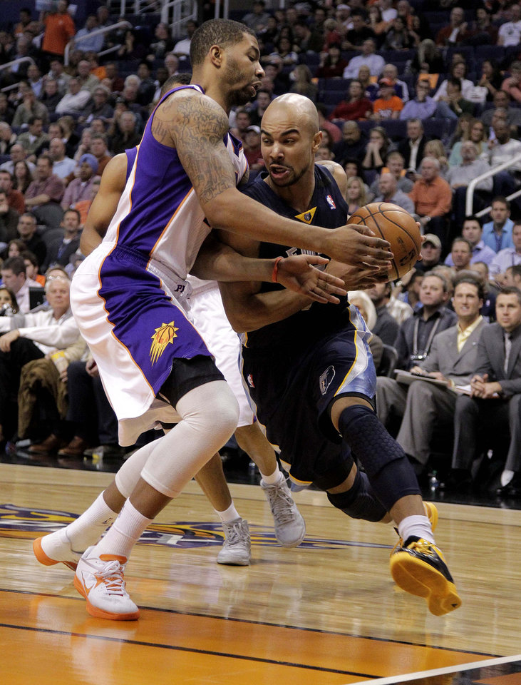 Memphis Grizzlies' Jerryd Bayless, right, drives against Phoenix Suns' Markieff Morris  during the first half of an NBA basketball game on Wednesday, Dec. 12, 2012, in Phoenix. (AP Photo/Matt York)