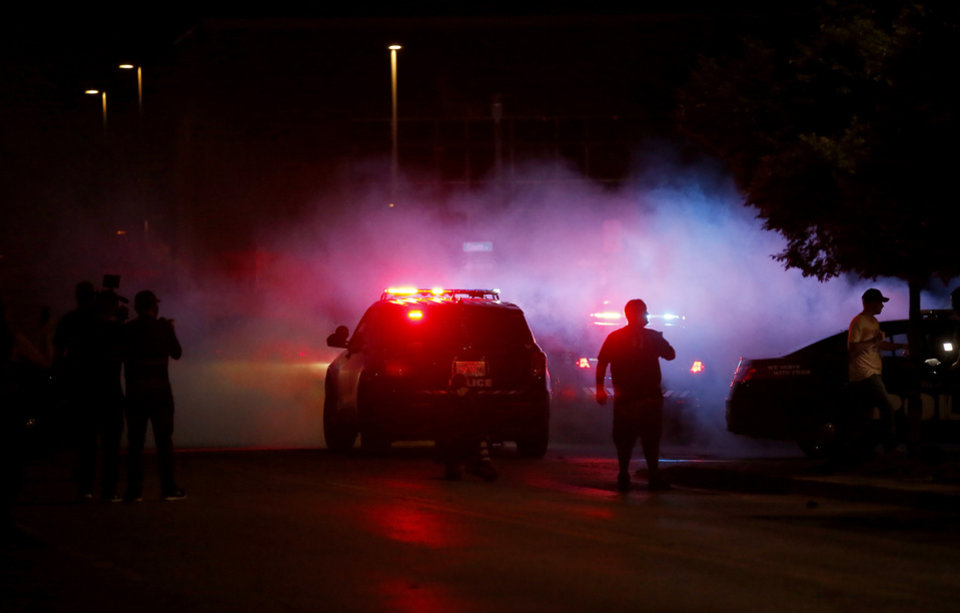 Photo - Protesters walk in front of the Oklahoma City Police Department as a tear gas cloud goes in the air in Oklahoma City, Saturday, May 30, 2020. The protest was in response to the death of George Floyd. [Sarah Phipps/The Oklahoman]