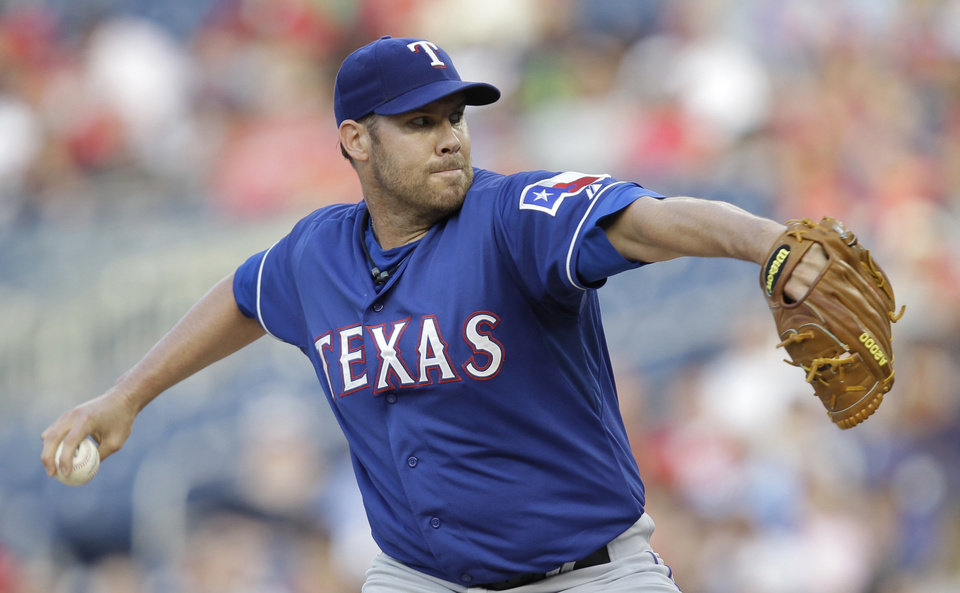 Photo - Texas Rangers starting pitcher Colby Lewis delivers the ball to the Washington Nationals during the first inning of a baseball game on Friday, May 30, 2014, in Washington. (AP Photo/Luis M. Alvarez)
