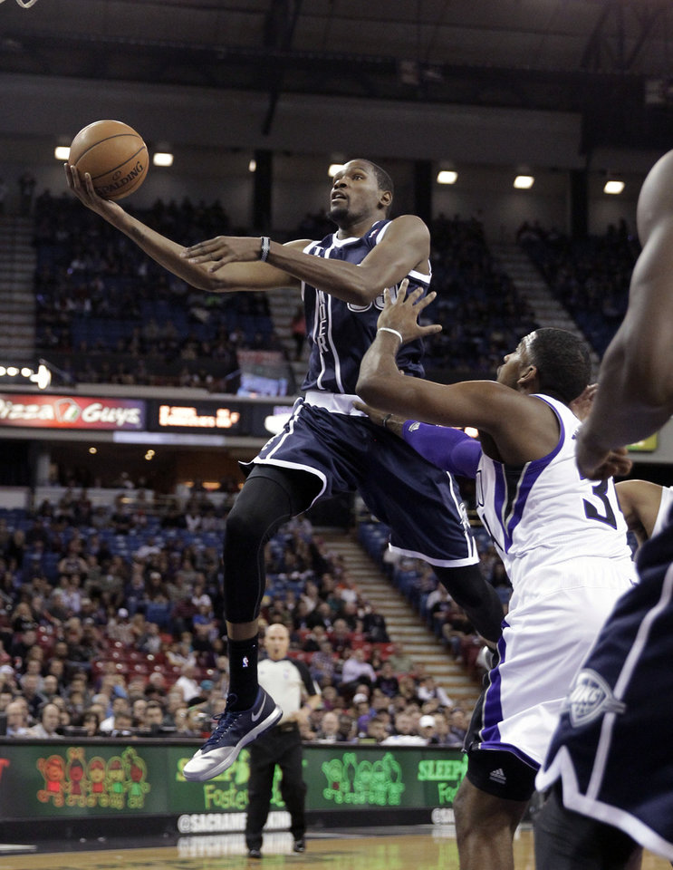 Oklahoma City Thunder forward Kevin Durant, left, drives to the basket against Sacramento Kings\' Jason Thompson during the first quarter of an NBA basketball game in Sacramento, Calif., Tuesday, Dec. 3, 2013. (AP Photo/Rich Pedroncelli)