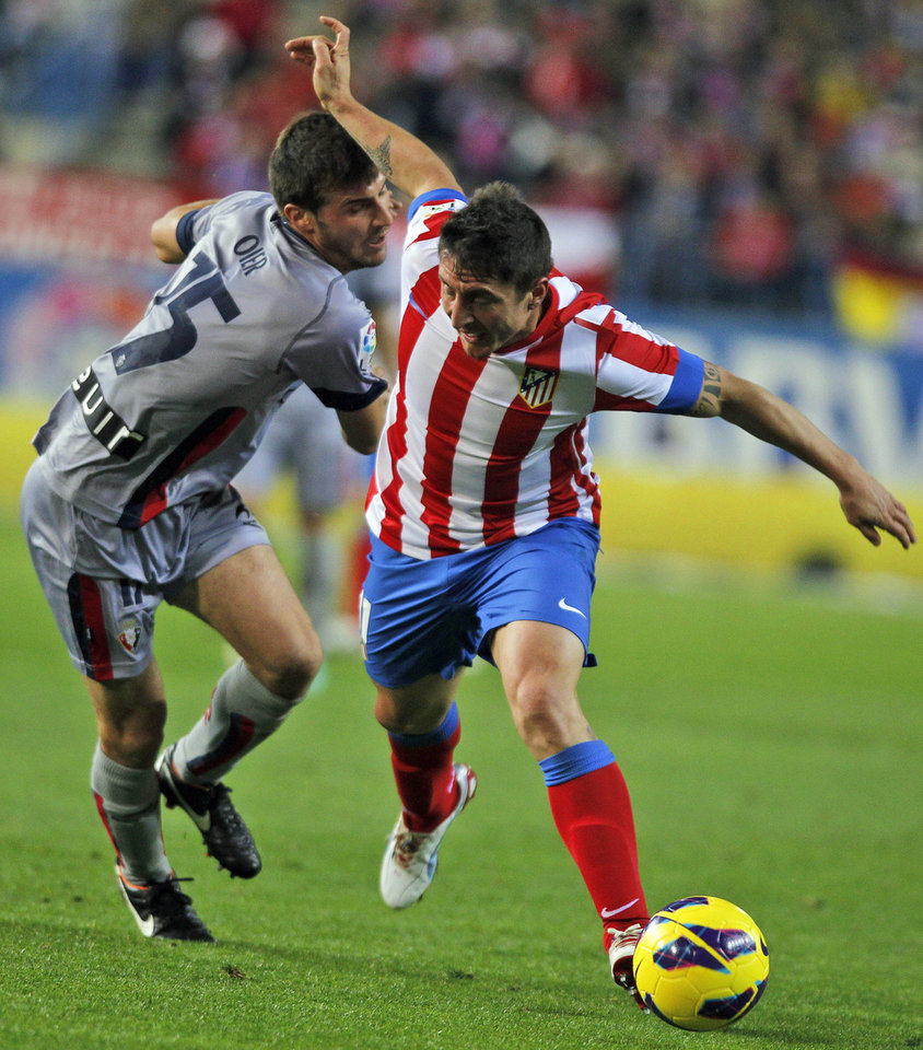 Photo -   Atletico de Madrid's Cristian Rodriguez from Uruguay, right, in action with Osasuna's Oier Sanjurjo, left, during a Spanish La Liga soccer match at the Vicente Calderon stadium in Madrid, Spain, Sunday, Oct. 28, 2012. (AP Photo/Andres Kudacki)