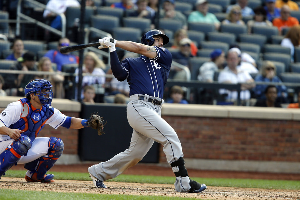 Photo - San Diego Padres' Yonder Alonso, right, follows through on a ground-rule double during the sixth inning of a baseball game against the New York Mets, Saturday, June 14, 2014, in New York. (AP Photo/Jason DeCrow)