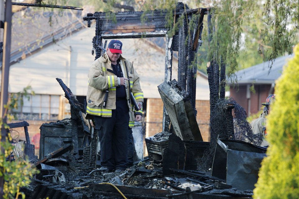 Photo -  Firefighters investigate a fatal house fire Tuesday at 1310 SW 23 in Oklahoma City. An explosion caused the blaze and killed a 6-year-old boy. Photo by Paul B. Southerland, The Oklahoman   PAUL B. SOUTHERLAND -