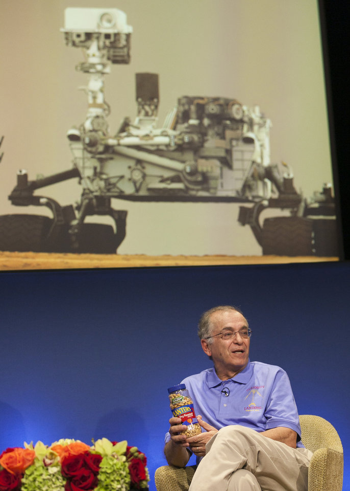 "NASA Jet Propulsion Laboratory (JPL) director Charles Elachi presents a can of ""good luck"" peanuts during an overview of the status and plans for NASA's Science Mission Directorate at JPL in Pasadena, Calif., Sunday, Aug. 5, 2012. After traveling 8 1/2 months and 352 million miles, Curiosity will attempt a landing on Mars Sunday night. In keeping with a decades-old tradition, peanuts will be passed around the mission control room at the NASA Jet Propulsion Laboratory for good luck. (AP Photo/Damian Dovarganes)"