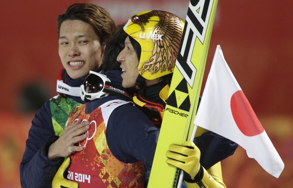 Photo - Japan's Taku Takeuchi, left, Reruhi Shimizu and Noriaki Kasai, from left, celebrate winning the bronze during the ski jumping large hill team competition at the 2014 Winter Olympics, Monday, Feb. 17, 2014, in Krasnaya Polyana, Russia. (AP Photo/Matthias Schrader)