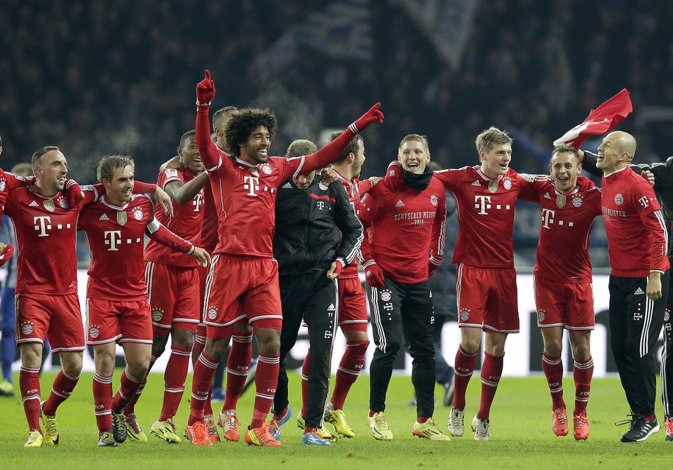Photo - Bayern's Arjen Robben of the Netherlands, right, Bayern's Franck Ribery of France, left, and their teammates celebrate winning the German soccer championship after the German Bundesliga soccer match between Hertha BSC Berlin and Bayern Munich in Berlin, Germany, Tuesday, March 25, 2014. (AP Photo/Michael Sohn)