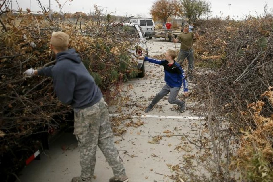 Photo -  Contract crews in Oklahoma City on Monday begin the months-long task of picking up residential debris from late October's ice storm. Here, Isaac Schweitzer, 12, unloads storm debris Saturday at a collection site at Griffin Park in Norman. [Bryan Terry/The Oklahoman]