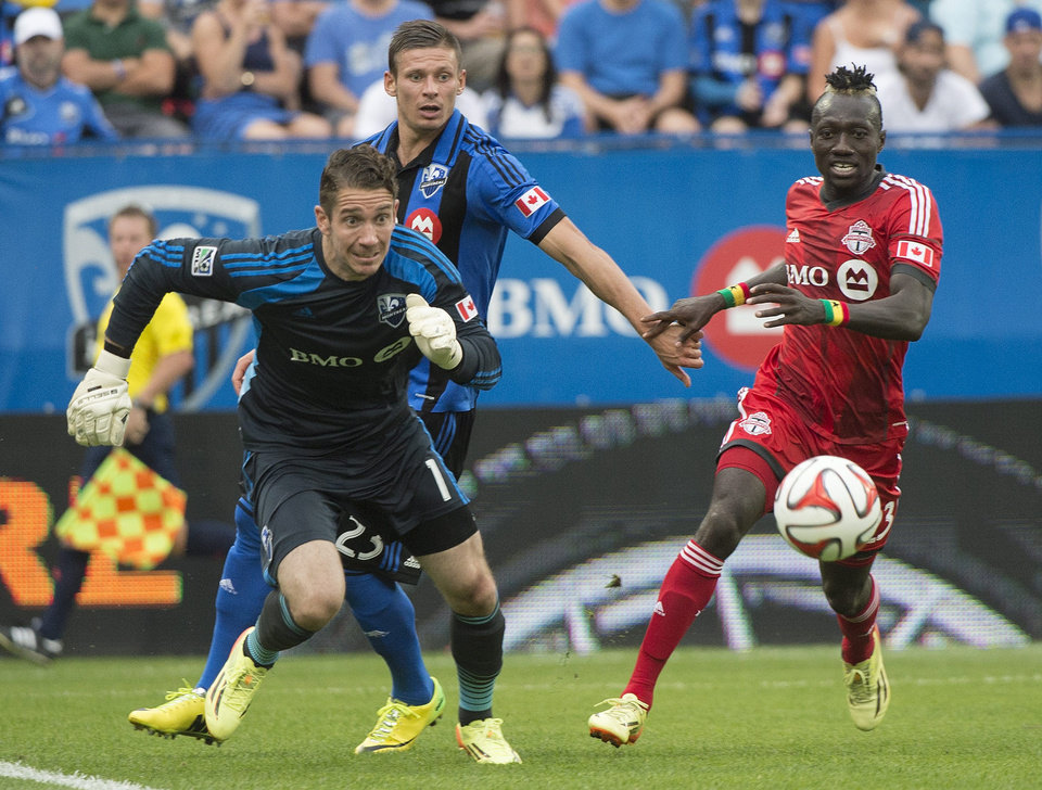 Photo - Montreal Impact's goalkeeper Troy Perkins, left, scrambles for the ball as Impact's Krzysztof Krol and Toronto FC's Dominic Oduro, right, look on, during the second half of a soccer match in Montreal, Saturday, Aug. 2, 2014. (AP Photo/The Canadian Press, Graham Hughes)