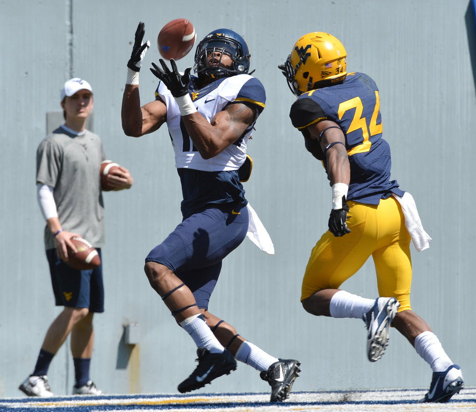 Photo - West Virginia's Kevin White (11) hauls in a touchdown pass while defended by Ishmael Banks during spring NCAA college football game in Morgantown, W.Va., Saturday, April 12, 2014. (AP Photo/Craig Cunningham)