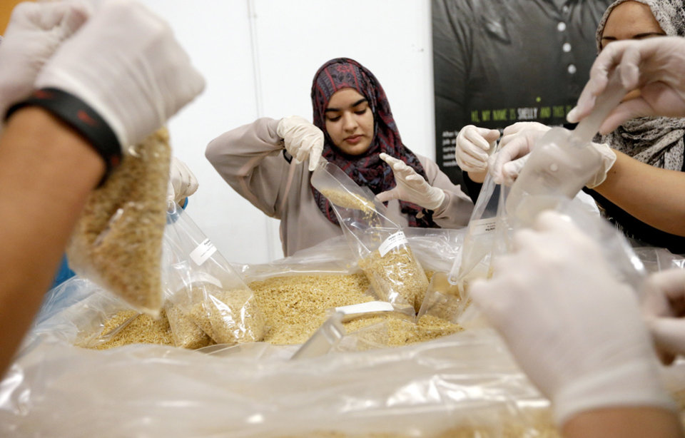 Photo - Zoha Qureshi packages rice while volunteering during the fasting hours of Ramadan at the Regional Food Bank of Oklahoma ,Saturday, July 27,  2013, in Oklahoma City. About 150 Muslims from various  organizations from across the state volunteered. Photo by Sarah Phipps, The Oklahoman