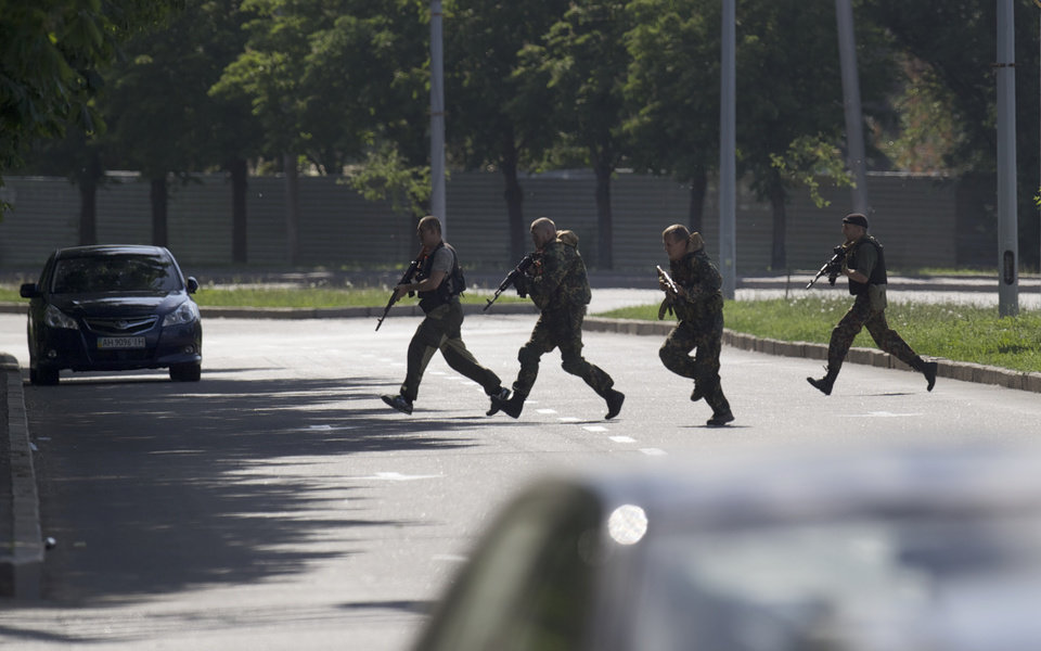 Photo - Pro-Russian insurgents  carrying weapons arrive near the airport outside Donetsk, Ukraine, Monday, May 26, 2014. Ukraine's military launched airstrikes Monday against the separatists who had taken over the airport in the eastern city of Donetsk, suggesting that fighting in the east is far from over. (AP Photo/Vadim Ghirda)