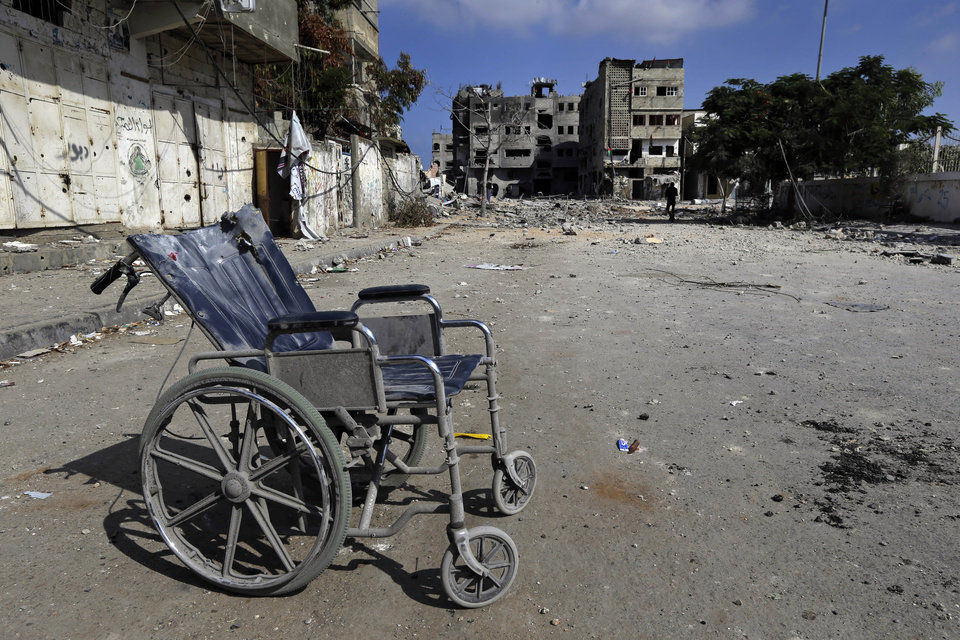 Photo - A wheelchair lies abandoned on a debris-strewn street amid the rubble of houses damaged by Israeli strikes in Beit Hanoun, northern Gaza Strip, Sunday, July 27, 2014. Hamas on Sunday agreed to observe a 24-hour humanitarian truce ahead of a major Muslim holiday after initially rejecting such an offer by Israel, as the two sides wrangled over setting the terms of a lull the international community hopes can be expanded into a more sustainable truce. (AP Photo/Lefteris Pitarakis)