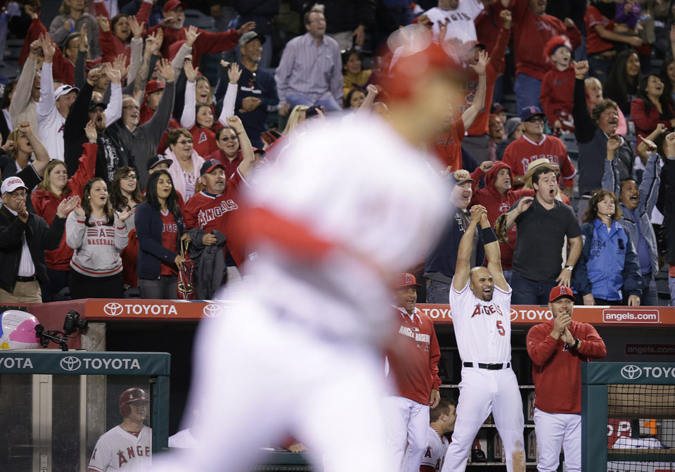 Photo - Fans cheer as Los Angeles Angels' Raul Ibanez, foreground, rounds the bases after hitting a three-run home run during the ninth inning of a baseball game against the New York Mets on Saturday, April 12, 2014, in Anaheim, Calif. (AP Photo/Jae C. Hong)