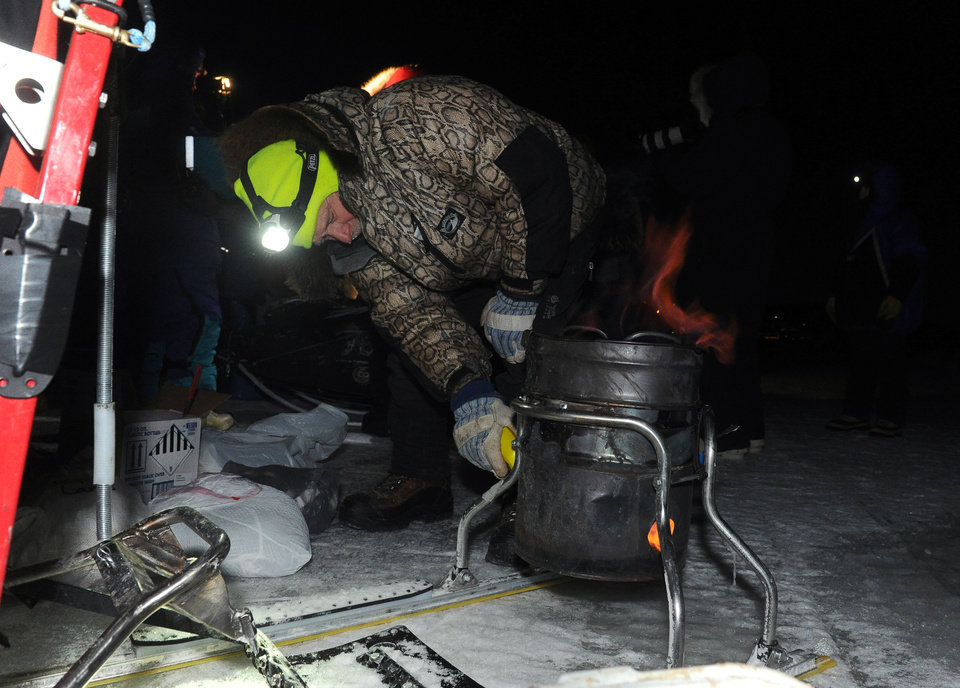 Photo - Iditarod musher Jeff King, from Denali, Alaska,  adds heat to his dog food cooker after arriving first into the White Mountain checkpoint during the Iditarod Trail Sled Dog Race on Monday, March 10, 2014. (AP Photo/The Anchorage Daily News, Bob Hallinen)