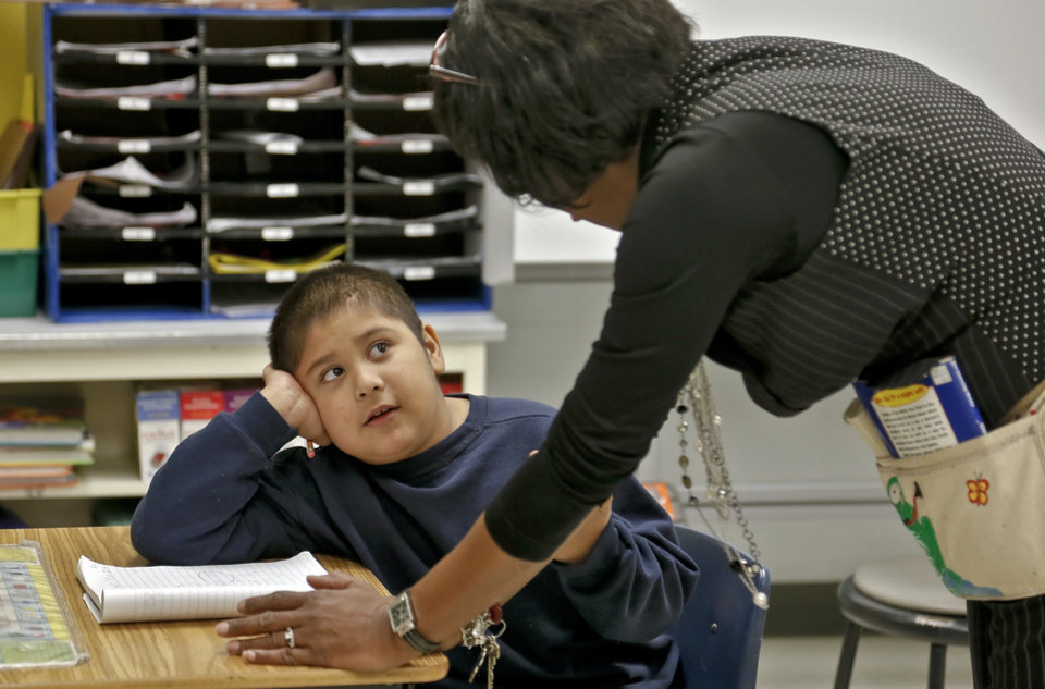 Second grade teacher Tonda Smith works with Victor Garza at North Highland Elementary on Tuesday, Jan. 15, 2013, in Oklahoma City, Okla. The school has been one of the most effected in the metro by the arrival of flu season.   Photo by Chris Landsberger, The Oklahoman