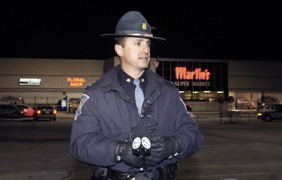Photo - Indiana State Police public information officer Sgt. Trent Smith talks to the media at the scene of a shooting  at Martin's Supermarket in Elkhart, Ind., late Wednesday, Jan. 15, 2014.   A man fatally shot two women inside the grocery store and was lining up to shoot a third person when police officers tracked him down and killed him, authorities said. Elkhart police received a call about a gunman at Martin's Super Market about 10 p.m. Wednesday, Smith said Thursday. The 22-year-old gunman used a semi-automatic handgun to shoot and kill a 20-year-old employee and a 44-year-old shopper, Smith said. The victims' bodies were found about 12 aisles apart. (AP Photo/The Elkhart Truth, Jon Garcia)
