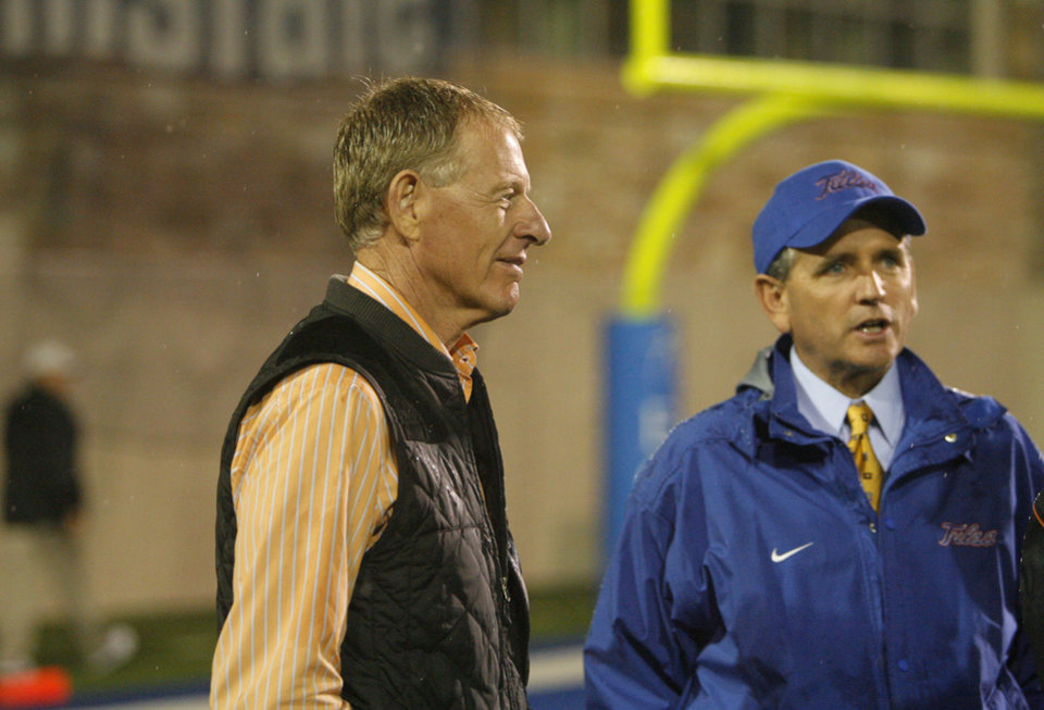 Photo - Oklahoma State athletic director Mike Holder and Tulsa athletic director Bubba Cunningham talk during a weather delay at a college football game between the Oklahoma State University Cowboys  and the University of Tulsa Golden Hurricane at H.A. Chapman Stadium in Tulsa, Okla., Saturday, Sept. 17, 2011. Photo by Sarah Phipps, The Oklahoman
