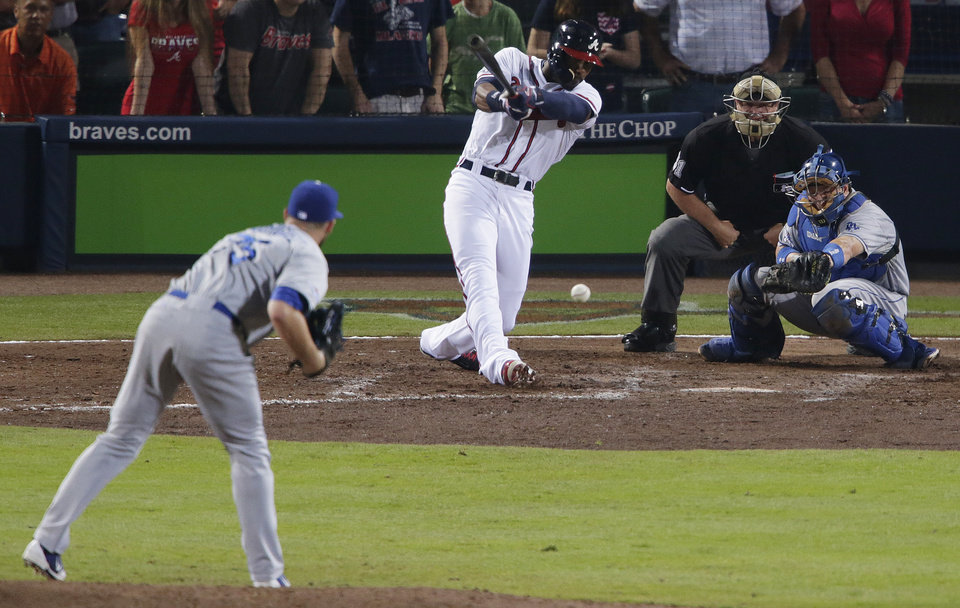 Photo - Atlanta Braves' Jason Heyward, center, hits a two-RBI single, scoring teammates Justin Upton and Chris Johnson, in the seventh inning of Game 2 of the National League division series against the Los Angeles Dodgers, Friday, Oct. 4, 2013, in Atlanta. (AP Photo/Dave Martin)