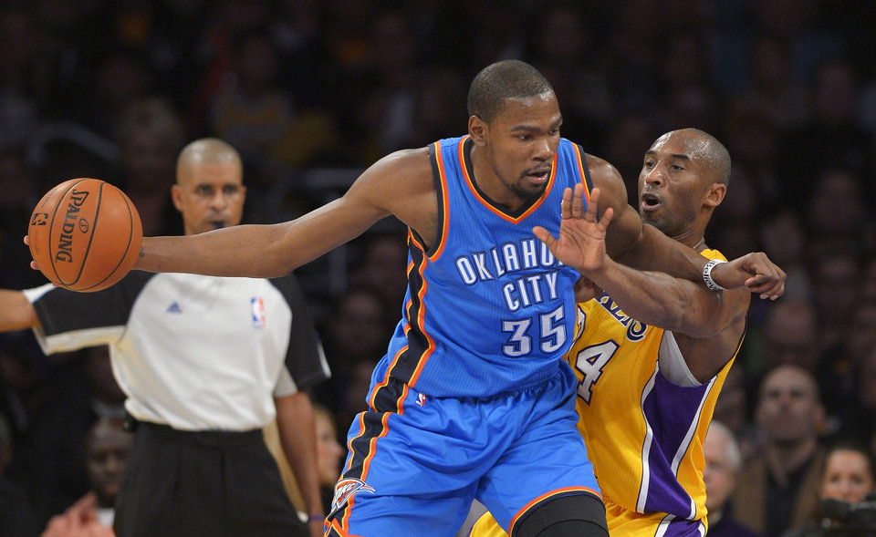 Oklahoma City Thunder forward Kevin Durant moves past Los Angeles Lakers guard Kobe Bryant during the first half of their NBA basketball game, Friday, Jan. 11, 2013, in Los Angeles. (AP Photo/Mark J. Terrill)