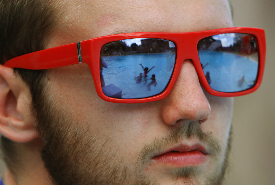 Children playing in the municipal pool are reflected in the lenses of lifeguard Weston Foote's sunglasses Wednesday afternoon. The pool, in downtown Shawnee, recently opened again after being closed for repairs. <strong>Jim Beckel - THE OKLAHOMAN</strong>