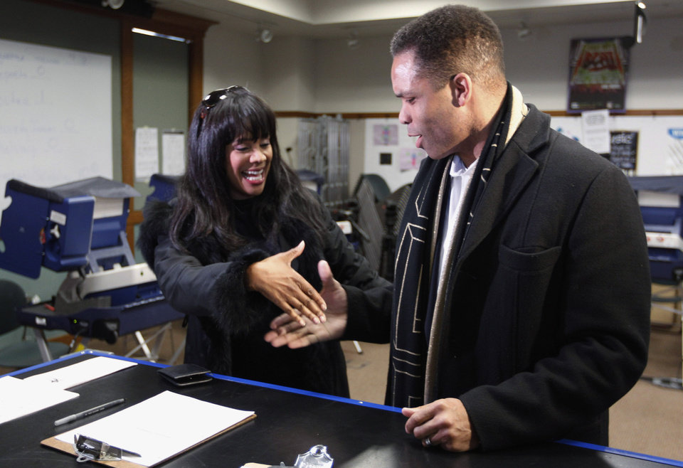 Photo - FILE - In this March 9, 2012 file photo, Rep. Jesse Jackson Jr. , D-Ill., and his wife, Chicago Alderman Sandi Jackson, ask each other for their support and votes as they arrive at a polling station for early voting in Chicago. The sweep of Jesse Jackson Jr.'s life, from golden boy who could be president to broken politician, will be laid out for a federal judge in Washington, D.C., Wednesday, Aug. 14, 2013, as she sentences him and his wife for misusing $750,000 in campaign money on a gold-plated Rolex watch, mink capes, mounted elk heads and other personal items. (AP Photo/M. Spencer Green, File)