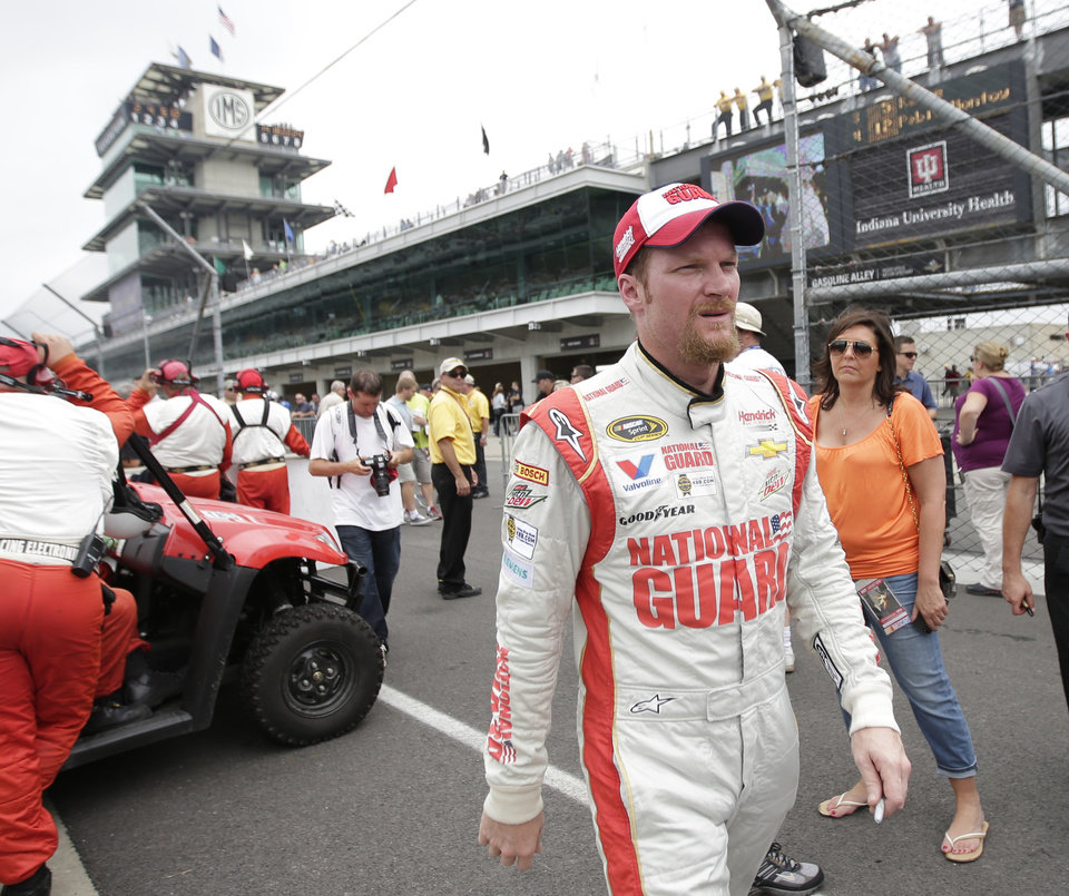 Photo - Dale Earnhardt Jr walks back to the garage after qualifying for the Brickyard 400 auto race at the Indianapolis Motor Speedway in Indianapolis, Saturday, July 26, 2014. (AP Photo/AJ Mast)