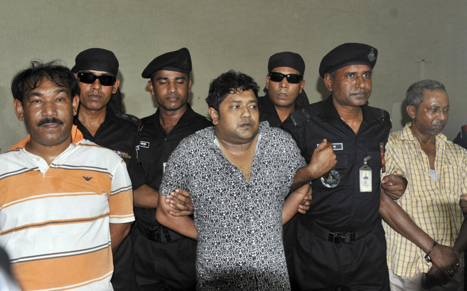 Mohammed Sohel Rana, center, the fugitive owner of an illegally-constructed building that collapsed last week in Bangladesh, killing some 377 people, is paraded by Rapid Action Battalion commandoes for the media along with his unidentified alleged accomplices, seen at left and right, in Dhaka, Bangladesh, Sunday, April 28, 2013.  Rana was arrested near the land border in Benapole in western Bangladesh, just as he was about to flee into India's West Bengal state, said Jahangir Kabir Nanak, junior minister for local government. (AP Photo)