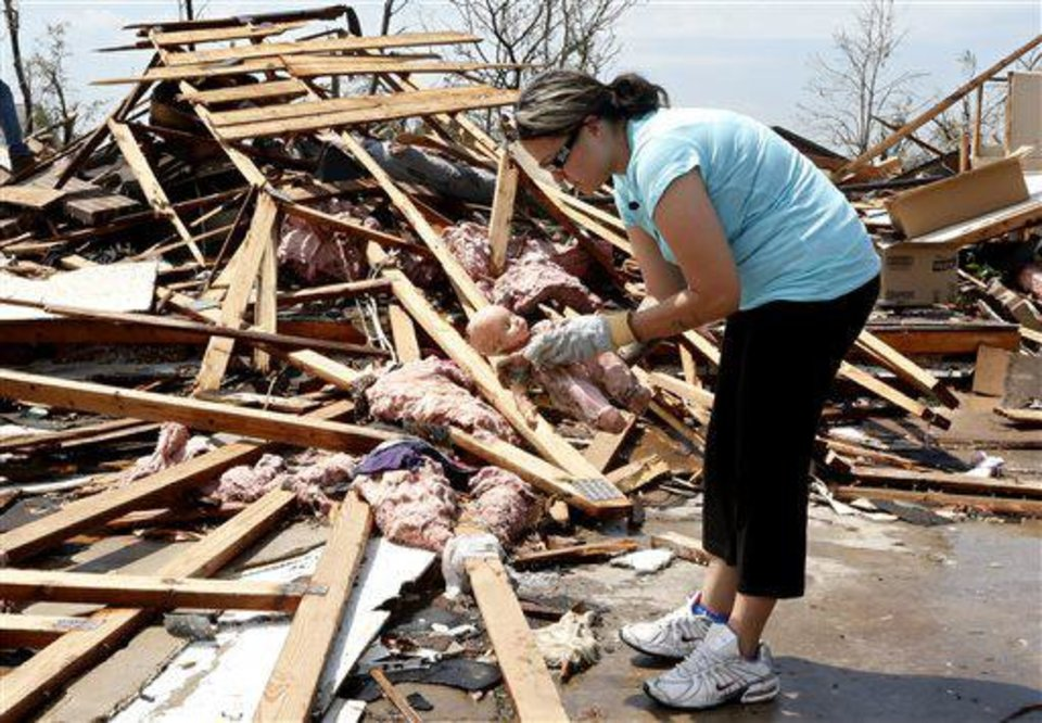 LaTisha Garcia finds a doll belonging to one of her daughters as she searches through the rubble of her tornado demolished home following Sunday's tornado in Moore, Okla., Thursday, May 23, 2013. (AP Photo/Sue Ogrocki)