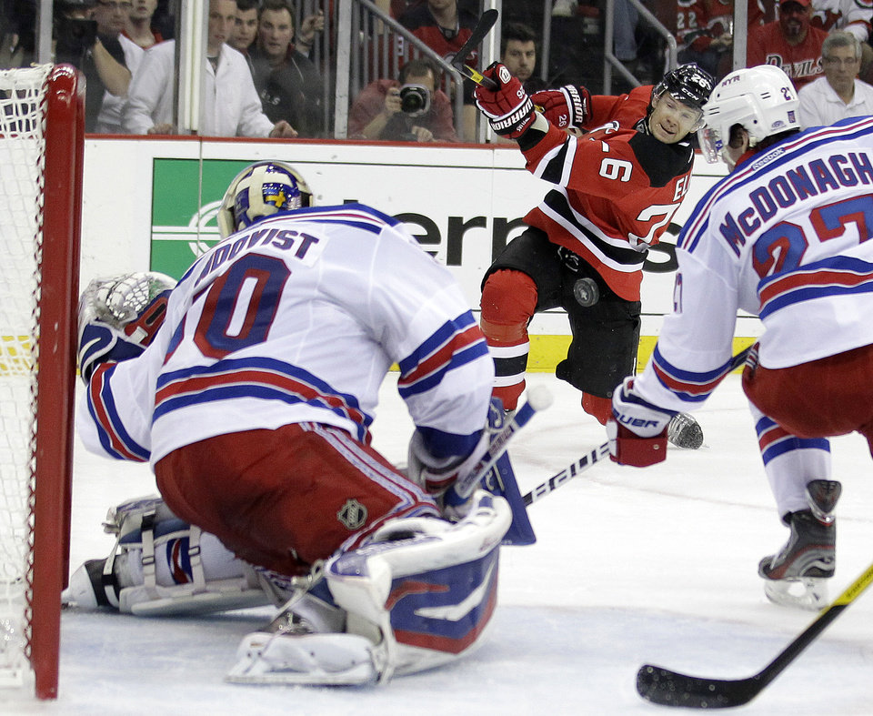 Photo -   New Jersey Devils' Patrik Elias, center, of Czech Republic, takes a shot against New York Rangers goalie Henrik Lundqvist, left, of Sweden, and Ryan McDonagh during the second period of Game 3 of an NHL hockey Stanley Cup Eastern Conference final playoff series, Saturday, May 19, 2012, in Newark, N.J. (AP Photo/Julio Cortez)