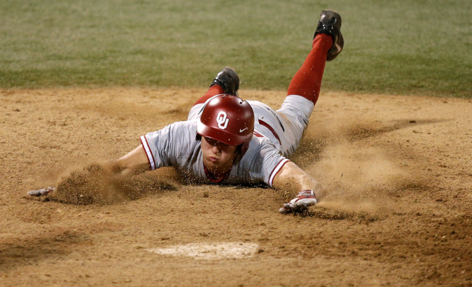 Photo - OU's Austin O'Brien slides home in the 18th inning of a Bedlam baseball game between Oklahoma State University and the University of Oklahoma in Stillwater, Tuesday, April 15, 2014. Photo by Bryan Terry, The Oklahoman