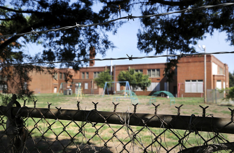 Photo -  Fencing surrounds the now-closed Dunbar Elementary at 1432 NE 7. [Photo by Jim Beckel, The Oklahoman Archives]